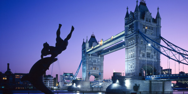 Silhouetted fountain statue and Tower Bridge illuminated at night, London, England, UK *** Local Caption ***