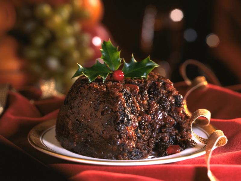 In questa immagine, c'è un Christmas pudding preparato per il pranzo di Natale. Questo dolce tipico inglese, da un lato, è già stato aperto per mostrare il ripieno all'interno. Il Christmas pudding è posto in un piatto bianco con bordi dorati e su un tavolo rosso. A scopo puramente scenografico, sulla torta vengono adagiate 3 foglie di Pungitopo.