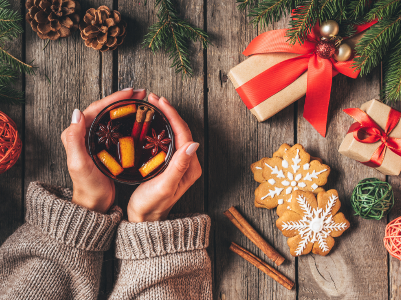 In questa foto, vengono mostrate le mani della ragazza che tengono un bicchiere di vin brulè. All'interno del bicchiere ci sono bucce d'arancia, 2 bastoncini di cannella e 2 fiori di anice stellato. La ragazza è vicino a un albero di Natale sotto il quale ci sono dei regali, delle pigne e dei biscotti.